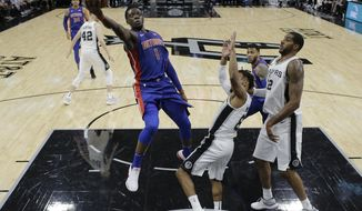 Detroit Pistons guard Reggie Jackson (1) shoots over San Antonio Spurs guard Patty Mills (8) during the first half of an NBA basketball game, Monday, Dec. 4, 2017, in San Antonio. (AP Photo/Eric Gay)