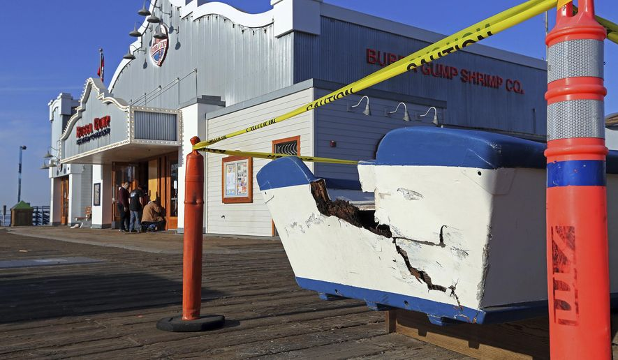 Workers view a boarded-up door where earlier a car, after clipping the boat in foreground, had crashed into the Bubba Gump Shrimp Co. restaurant on the Santa Monica Pier after an altercation between people in the vehicle and construction workers on the pier in Santa Monica, Calif., early Monday, Dec. 4, 2017. One worker suffered minor injuries but no one was transported to a hospital following the incident shortly before 5 a.m. Monday. The driver was taken into custody. (AP Photo/Reed Saxon)