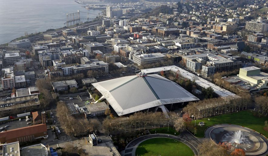 The iconic sloped roof of KeyArena, center, a sports and entertainment venue at the Seattle Center, is seen from above Monday, Dec. 4, 2017, in Seattle. The Seattle City Council on Monday approved a memorandum of understanding with Los Angeles-based Oak View Group in a $600 million privately financed project to renovate the facility, formerly the home of the NBA's SuperSonics. (AP Photo/Elaine Thompson)