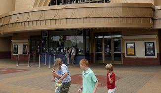 In this Tuesday July 26, 2011, file photo, people walk past Regal Entertainment's Palladium Cinemas in High Point, N.C. Cineworld is paying $3.61 billion for Regal Entertainment as it expands its global footprint. Cineworld has theaters in several nations, while Regal operates theaters throughout the U.S. (Don Davis Jr./The High Point Enterprise via AP, File)