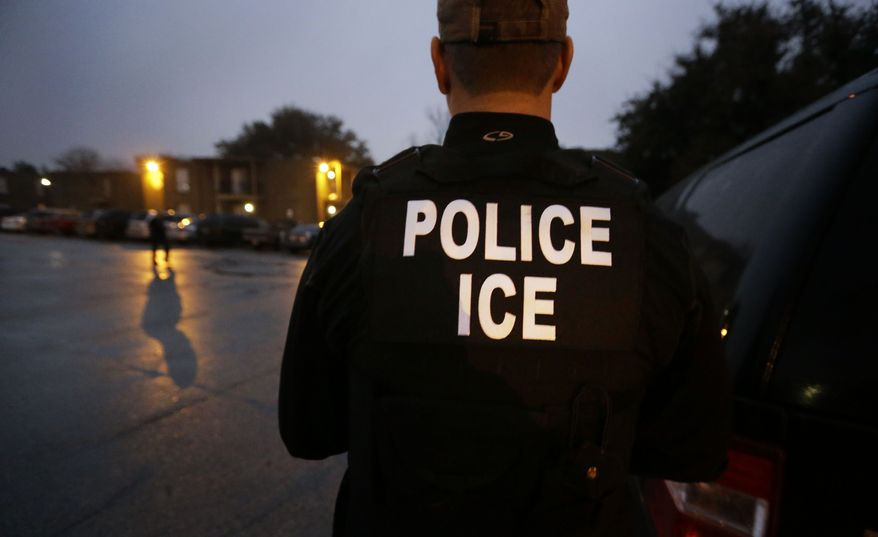 In this March 6, 2015, file photo, U.S. Immigration and Customs Enforcement agents enter a Dallas apartment complex looking for a specific undocumented immigrant convicted of a felony. (AP Photo/LM Otero, File) ** FILE **