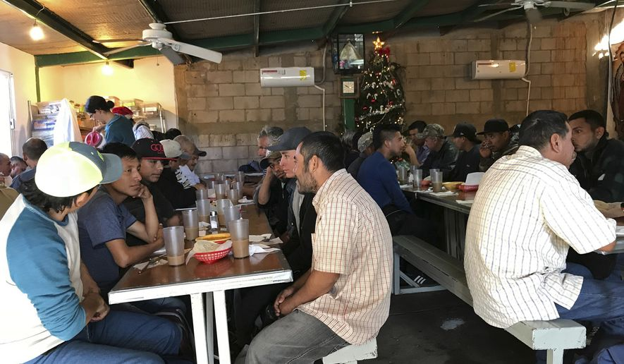 In this photo taken Monday, Dec. 4, 2017, some recently deported migrants eat breakfast at the dining room run by the nonprofit Kino Border Initiative in Nogales Mexico. The federal government on Tuesday, Dec. 5, 2017, issued its most complete statistical snapshot of immigration enforcement under President Donald Trump, saying Border Patrol arrests plunged to a 45-year low while arrests by deportation officers soared. (AP Photo/Anita Snow)