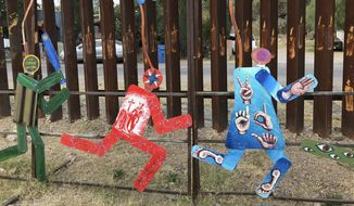 Artistic figures in Nogales, Mexico, portray a U.S. Border Patrol officer chasing several migrants. The federal government on Tuesday issued its most complete statistical snapshot of immigration enforcement under President Trump, saying Border Patrol arrests plunged to a 45-year low while arrests by deportation officers soared. (Associated Press)