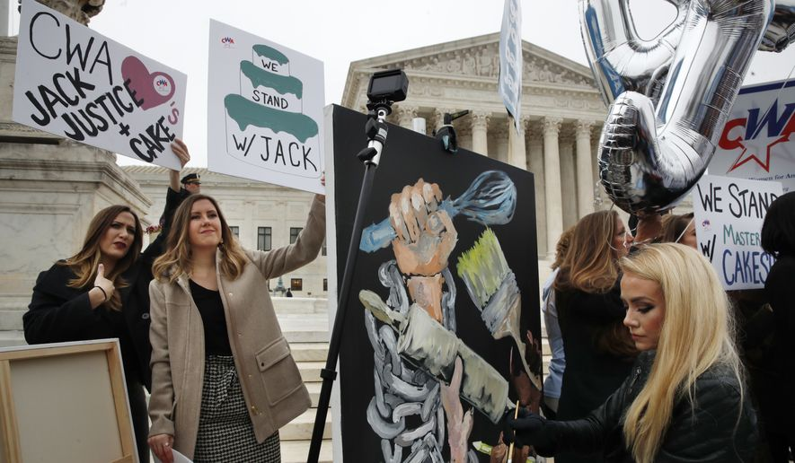 As Janae Stracke, left, and Annabelle Rutledge, both with Concerned Women for America, hold up signs, as Jessica Haas, of Indianapolis, paints during a rally with supporters of cake artist Jack Phillips outside of the Supreme Court which is hearing the 'Masterpiece Cakeshop v. Colorado Civil Rights Commission' today, Tuesday, Dec. 5, 2017, in Washington. (AP Photo/Jacquelyn Martin)