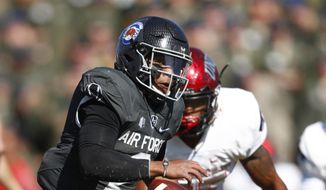 In this Saturday, Oct. 14, 2017 file photo, Air Force quarterback Arion Worthman, front, runs for a short gain as UNLV linebacker Gabe McCoy pursues in the second half of an NCAA college football game at Air Force Academy, Colo. The triple option has been part of the DNA for Air Force, Navy and Army for decades because it levels the playing field. It's hard to defend and doesn't require big offensive linemen. At its core, the system is centered on a quarterback with plenty of moxie and a fullback with a nose for getting through a tiny crease.  (AP Photo/David Zalubowski, File) **FILE**