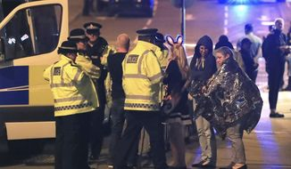 FILE - This s a May 23, 2017 file photo of members of the  emergency services  attending the scene at Manchester Arena after reports of an explosion at the venue during an Ariana Grande gig. An independent review of the counter-terrorism performance by British police and intelligence services rleease on Tuesday Dec. 5, 2017  suggested that the deadly suicide bombing at Manchester Arena might have been prevented if information had been handled differently.  (Peter Byrne/PA, File via AP)