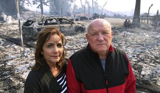 """Linda and John Keasler pose for a photo in front of the ruins of their home at the Hawaiian Village Apartments, destroyed when the Thomas fire swept through Ventura, Calif., Tuesday, Dec. 5, 2017. """"It is sad. We loved this place. We lost everything,"""" John Keasler, 65, said. (AP Photo/Amanda Lee Myers)"""