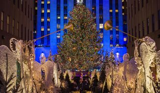 FILE - In this Nov. 29, 2017, file photo, the Rockefeller Center Christmas tree stands lit as people take photos of it and the holiday decorations at Rockefeller Center during the 85th annual Rockefeller Center Christmas tree lighting ceremony in New York. For the past decade, old Rockefeller Center Christmas trees have gone on to be milled into lumber used in dozens of Habitat for Humanity homes from Philadelphia to Pascagoula, Mississippi. (AP Photo/Andres Kudacki, File)