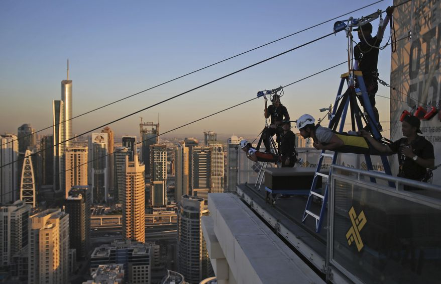 Two people prepare to ride the world's longest urban zip line, with a speed of up to 80 kilometers per hour on a one kilometer run from 170 meter to ground level, in the Marina district of Dubai, United Arab Emirates, Tuesday, Dec. 5, 2017. (AP Photo/Kamran Jebreili)