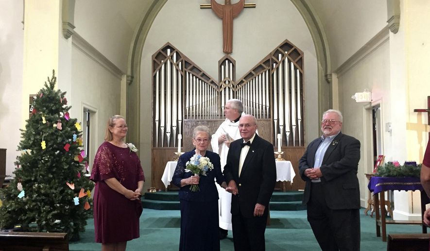 ADVANCE FOR USE SATURDAY, DEC. 9 - In this Saturday, Dec. 2, 2017 photo, Pat Mumme, 83, and Dale Eschilman, 89, center, were married, at SS Mary and Patrick Church in West Burlington, Iowa. The couple found love through an online dating site in Iowa. (Julia Mericle/The Hawk Eye via AP)