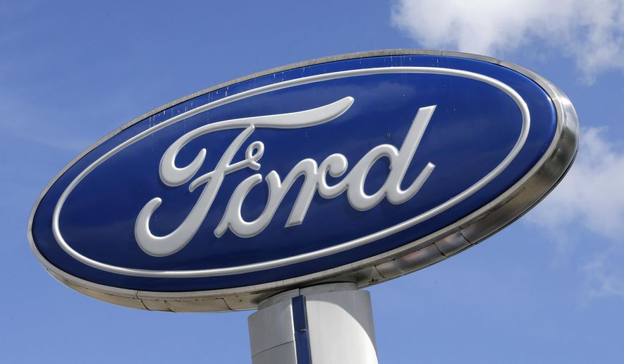 This Jan. 17, 2017, file photo shows a Ford sign at an auto dealership, in Hialeah, Fla. At least 30 percent of the new vehicles Ford will roll out in China by 2025 will be electric, with Beijing pushing hard to improve air quality for people living in smoke-choked cities. Ford said Tuesday, Dec. 5, that the new electric cars will fall under the Lincoln brand and its namesake. (AP Photo/Alan Diaz, File)