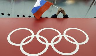FILE - In this Feb. 18, 2014, file photo, a Russian skating fan holds the country's national flag over the Olympic rings before the start of the men's 10,000-meter speedskating race at Adler Arena Skating Center during the 2014 Winter Olympics in Sochi, Russia. Russia could be banned from competing at the Pyeongchang Olympics. The decision will come on Tuesday, Dec. 5, 2017 when the International Olympic Committee executive board meets in Lausanne, less than nine weeks before the games open on Feb. 9 in South Korea. (AP Photo/David J. Phillip, File)