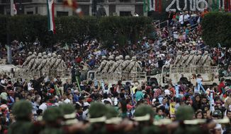 FILE - In this Sept. 16, 2016 file photo, people watch soldiers during the annual Independence Day military parade in Mexico City's main square, known as the Zocalo. Mexico's National Human Rights Commission denounced on Dec. 5, 2017 a case of alleged abuses in 2016 by members of the military, which is heavily involved in prosecuting the country's war against drug gangs. (AP Photo/Rebecca Blackwell, File)