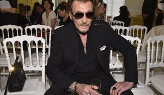FILE - In this July 4, 2016 file picture, French rock singer Johnny Hallyday waits before Christian Dior's Haute Couture Fall-Winter 2016-2017 fashion collection presented in Paris, France. The French president's office says Hallyday, who packed sports stadiums for decades, has died at age 74. (AP Photo/Zacharie Scheurer, File)