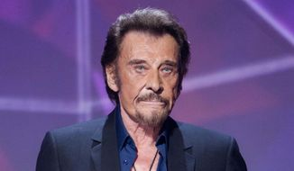 In this Friday, Feb. 12, 2016, file picture, French singer Johnny Hallyday gestures as he receives the best chanson album award during the 31st Victoires de la Musique, French music awards annual ceremony, in Paris, France. The French president's office says Hallyday, who packed sports stadiums for decades, has died at age 74. (AP Photo/Jacques Brinon, File)