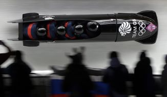 FILE - In this Feb.22, 2014 file photo, the team from Great Britain GBR-1, with John James Jackson, Stuart Benson, Bruce Tasker and Joel Fearon, take a curve on their first run during the men's four-man bobsled competition at the 2014 Winter Olympics, in Krasnaya Polyana, Russia. The British team, which placed fifth at the time, is now in line to get the bronze medal after two Russian sleds in front of them were disqualified for doping. The International Olympic Committee was deciding Tuesday whether to ban Russia from the 2018 Pyeongchang Games because of the doping scheme involving hundreds of athletes. (AP Photo/Dita Alangkara, File)