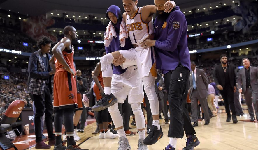 Phoenix Suns guard Devin Booker (1) is carried off by teammates during the second half of an NBA basketball game against the Toronto Raptors on Tuesday, Dec. 5, 2017, in Toronto. (Nathan Denette/The Canadian Press via AP)