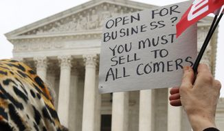 A woman holds up a sign as people gather outside of the Supreme Court which is hearing the 'Masterpiece Cakeshop v. Colorado Civil Rights Commission' today, Tuesday, Dec. 5, 2017, in Washington. (AP Photo/Jacquelyn Martin)