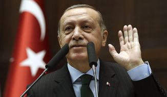 "Turkey's President Recep Tayyip Erdogan gestures as he delivers a speech to a meeting of his ruling Justice and Development Party (AKP), in Ankara, Turkey, Tuesday, Dec. 5, 2017. Erdogan is calling the New York trial of a Turkish banker a U.S. conspiracy being staged to ""blackmail"" and ""blemish"" his country. Erdogan said: ""Turkey has no plans against the United States, but it is clear that the U.S. has plans against us."" (Yasin Bulbul/Pool via AP)"