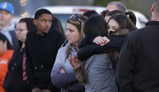 Two people hug as they wait to be reunited with students on lockdown near Graham-Kapowsin High School, Frontier Middle School, and Nelson Elementary School, Tuesday, Dec. 5, 2017, in Graham, Wash. Authorities said two students were shot near the high school Tuesday afternoon. (AP Photo/Ted S. Warren)