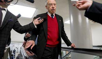 Sen. Chuck Grassley, R-Iowa, speaks to reporters as he walks through the Senate subway on Capitol Hill, Wednesday, Dec. 6, 2017, in Washington. (AP Photo/Andrew Harnik)