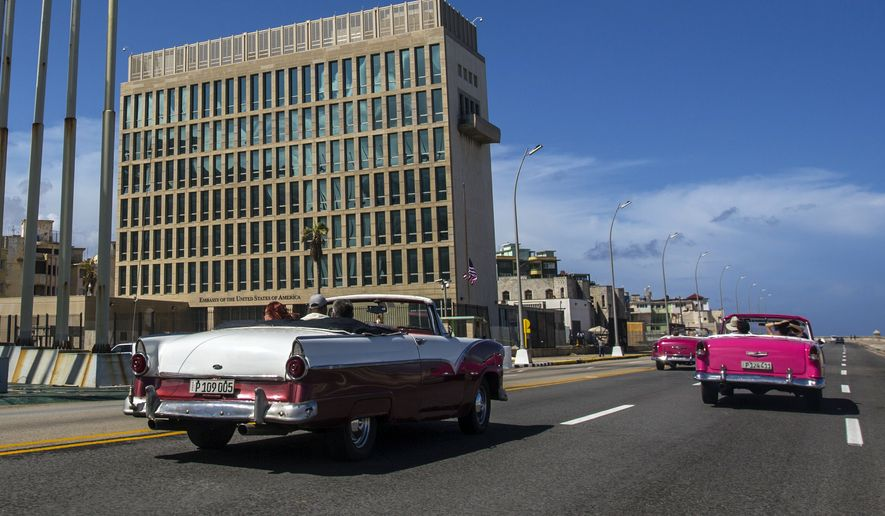 In this Oct. 3, 2017, file photo, tourists ride classic convertible cars on the Malecon beside the United States Embassy in Havana, Cuba. Doctors treating the U.S. Embassy victims of mysterious, invisible attacks in Cuba have discovered brain abnormalities as they search for clues to hearing, vision, balance and memory damage, The Associated Press has learned. (AP Photo/Desmond Boylan) ** FILE **