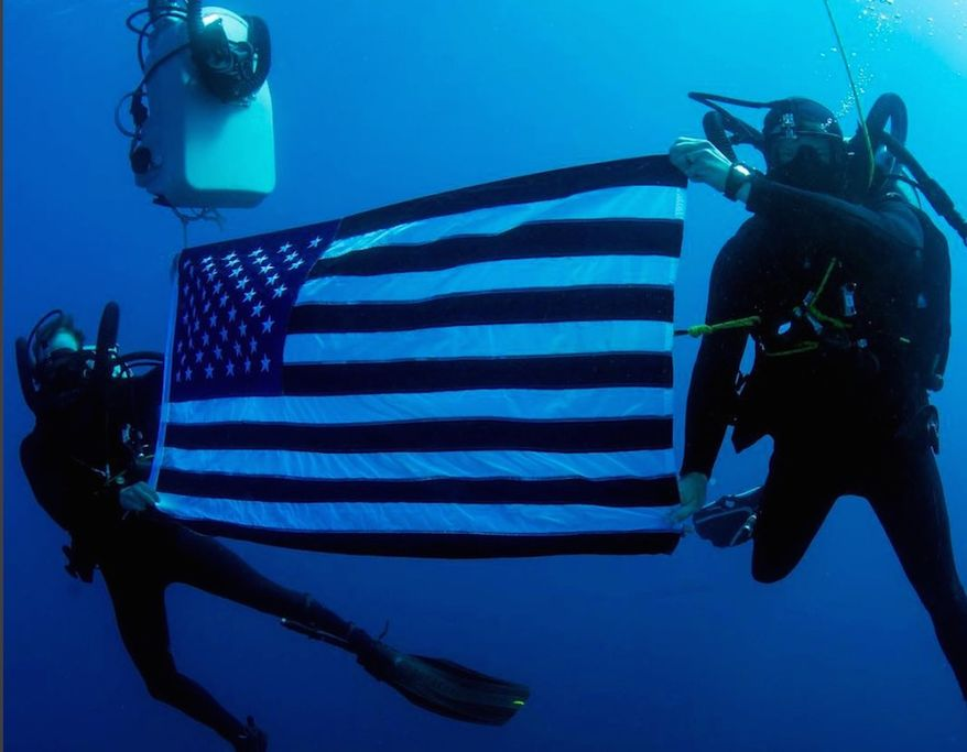 Explosive Ordnance Disposal Technicians with the U.S. Navy pose for a picture with an American flag. (Image: Instagram, U.S. Navy)