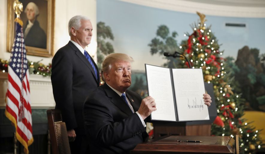 President Donald Trump, accompanied by Vice President Mike Pence, holds up a signed proclamation recognizing Jerusalem as the capital of Israel in the Diplomatic Reception Room of the White House, Wednesday, Dec. 6, 2017, in Washington.  (AP Photo/Alex Brandon)