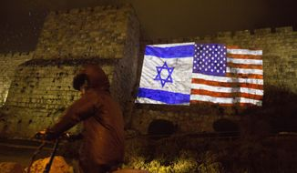 An ultra Orthodox Jewish man rides a bicycle as US and Israeli flags are projected on the walls of Jerusalem's old city, Wednesday, Dec. 6, 2017. The Jerusalem municipality has lit the walls of the Old City red, white and blue to show thanks to President Trump's recognition of it as Israel's capital. (AP Photo/Sebastian Scheiner)
