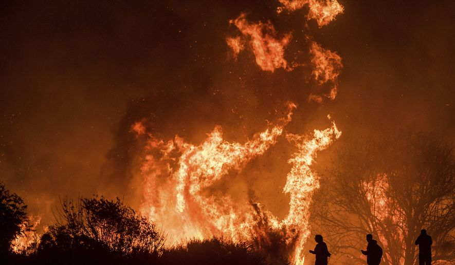 Motorists on Highway 101 watch flames from the Thomas fire leap above the roadway north of Ventura, Calif., on Wednesday, Dec. 6, 2017.  As many as five fires have closed highways, schools and museums, shut down production of TV series and cast a hazardous haze over the region. About 200,000 people were under evacuation orders. No deaths and only a few injuries were reported. (AP Photo/Noah Berger)