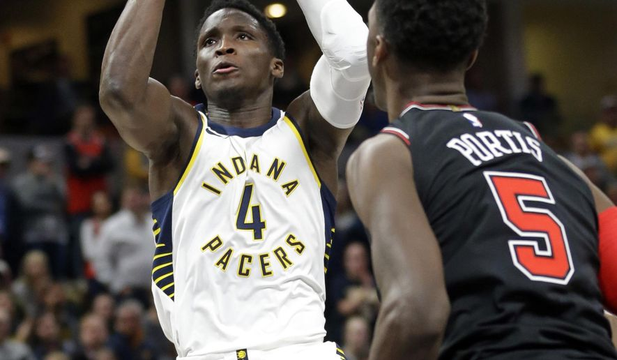 Indiana Pacers guard Victor Oladipo (4) shoots over Chicago Bulls forward Bobby Portis (5) during the second half of an NBA basketball game in Indianapolis, Wednesday, Dec. 6, 2017. The Pacers defeated the Bulls 98-96. (AP Photo/Michael Conroy)