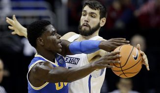 FILE- In this Nov. 20, 2017 file photo, Creighton's Manny Suarez, right, tries to block a pass by UCLA's Aaron Holiday, during an NCAA college basketball game in Kansas City, Mo. With one year of eligibility left, the 6-foot-10, 250-pounder Suarez transferred from Division II Adelphi to Division I Creighton, and he's playing a significant role off the bench. He's among fewer than 10 transfers who made the move from D2 to D1 this season. (AP Photo/Charlie Riedel, File)