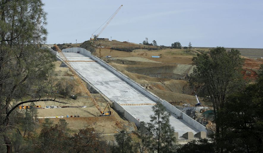 FILE - In this Nov. 30, 2017, file photo, work continues on the Oroville Dam spillway in Oroville, Calif. California water officials plan to update a Northern California community about their efforts to repair the nation's tallest dam after damage to its spillways forced nearly 200,000 people to evacuate last February. (AP Photo/Rich Pedroncelli, File)