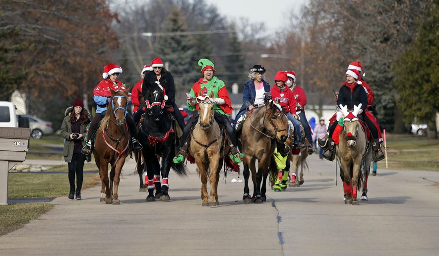 In this Dec. 2, 2017 photo, Christmas Caroling by Horseback move down a street in Fox Crossing, Wis. Dressed for the occasion, the riders hoped to raise awareness of horses that were rescued from slaughter by A Second Chance Equine Rescue in Larsen, Wis. (Ron Page/The Post-Crescent via AP)