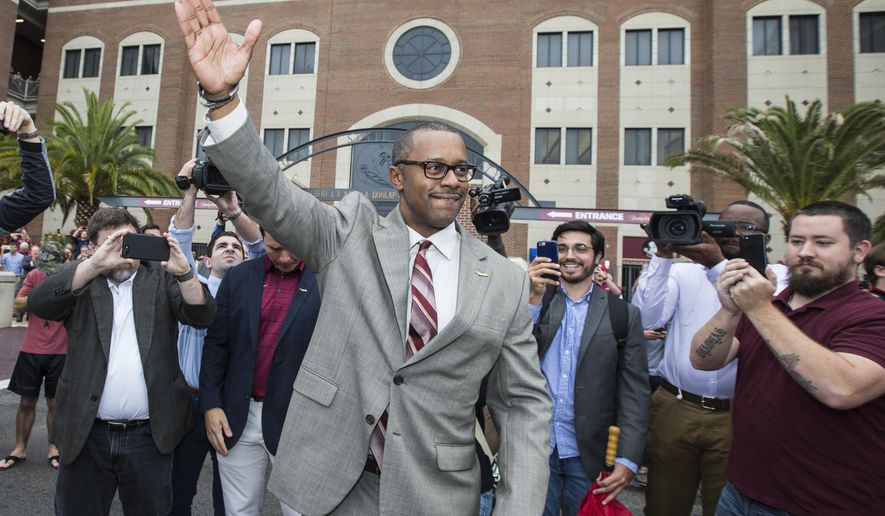 Willie Taggart does the Seminole chop in front of Doak Campbell Stadium before being introduced as Florida State University's new NCAA college football coach in Tallahassee, Fla., Wednesday, Dec. 6, 2017. (AP Photo/Mark Wallheiser)