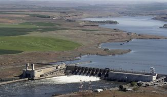 FILE - In this 2013 file photo, the Ice Harbor Dam on the Snake River is seen from the air near Pasco, Wash. Washington Gov. Jay Inslee is opposing a bill in Congress that would reduce spill over Columbia and Snake river dams, and prevent the breaching of four Snake River dams in eastern Washington state. In a letter to leaders of the House, the Democratic governor says the bill would harm ongoing efforts to improve salmon and dam management. (Bob Brawday/The Tri-City Herald via AP, File)