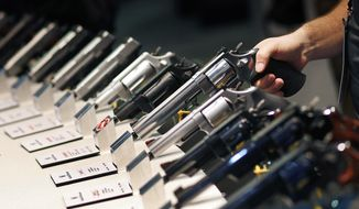 FILE - In this Jan. 19, 2016 file photo, handguns are displayed at the Smith & Wesson booth at the Shooting, Hunting and Outdoor Trade Show in Las Vegas. Backers of an expanded gun background check ballot measure approved by Nevada voters in 2016 are arguing that the Nevada governor and attorney general are wrong to say they can't enforce the law. (AP Photo/John Locher, File)