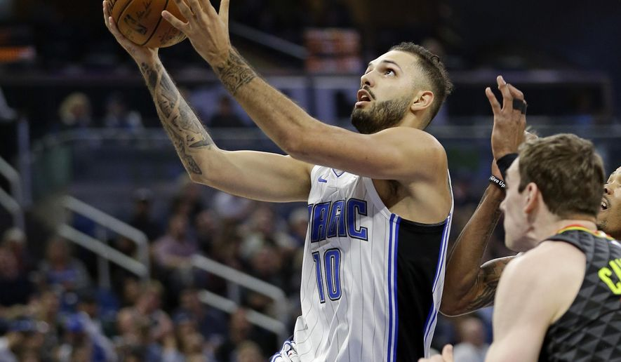 Orlando Magic's Evan Fournier (10) goes past Atlanta Hawks' Tyler Cavanaugh, right, for a shot during the first half of an NBA basketball game, Wednesday, Dec. 6, 2017, in Orlando, Fla. (AP Photo/John Raoux)