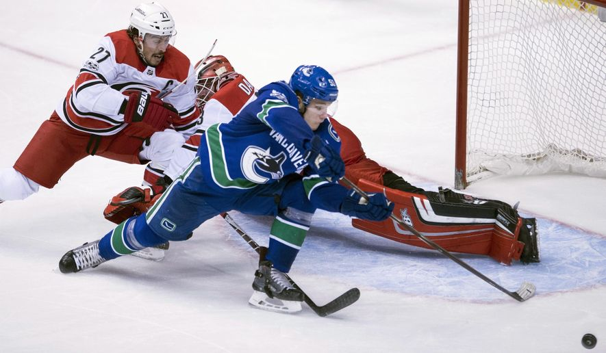 Carolina Hurricanes defenseman Justin Faulk (27) tries to stop Vancouver Canucks centre Bo Horvat (53) from getting a shot on Hurricanes goalie Scott Darling (33) during the second period of an NHL hockey game Tuesday, Dec. 5, 2017, in Vancouver, British Columbia. (Jonathan Hayward/The Canadian Press via AP)