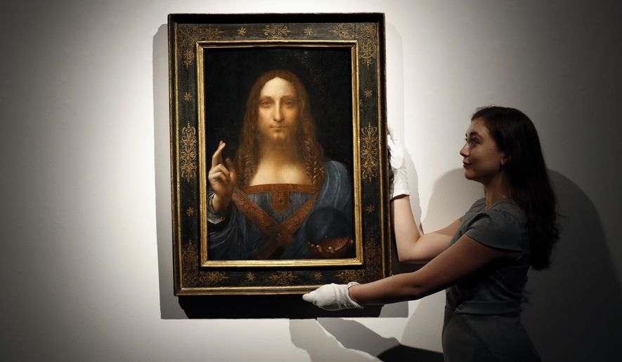 "FILE- In this Oct. 24, 2017 file photo, an employee poses with Leonardo da Vinci's ""Salvator Mundi"" on display at Christie's auction rooms in London. The rare painting of Christ, which that sold for a record $450 million, is heading to a museum in Abu Dhabi. The newly-opened Louvre Abu Dhabi made the announcement in a tweet on Wednesday, Dec. 6. (AP Photo/Kirsty Wigglesworth, File)"