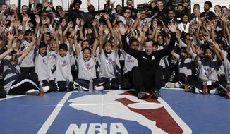 Brooklyn Nets players and coaches, including head coach Kenny Atkinson, front, pose for a picture with children after teaching them basketball skills in an NBA Cares event at the Maestro Miguel A. Quintana Primary School in Mexico City, Wednesday, Dec. 6, 2017. The Brooklyn Nets will play two regular season games in Mexico City, facing the Oklahoma City Thunder on Thursday, Dec. 7 and the Miami Heat on Saturday, Dec. 9. (AP Photo/Rebecca Blackwell)