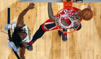 New Orleans Pelicans center DeMarcus Cousins (0) goes to the basket against Denver Nuggets forward Kenneth Faried, left, in the first half of an NBA basketball game in New Orleans, Wednesday, Dec. 6, 2017. (AP Photo/Gerald Herbert)