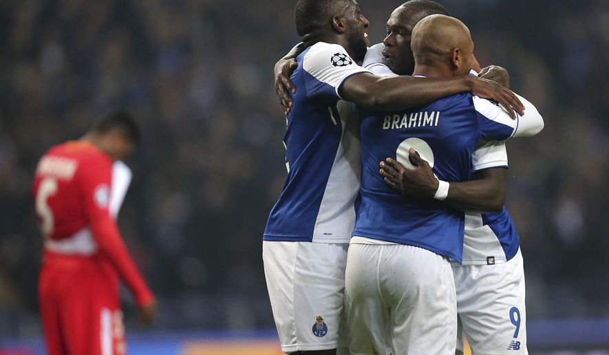 Porto's Yacine Brahimi, right, celebrates with Vincent Aboubakar, 2nd right, and Moussa Marega after scoring his side's third goal during the Champions League group G soccer match between FC Porto and AS Monaco at the Dragao stadium in Porto, Portugal, Wednesday, Dec. 6, 2017. (AP Photo/Luis Vieira)