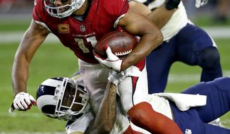 Arizona Cardinals wide receiver Larry Fitzgerald (11) is hit against the Los Angeles Rams during the second half of an NFL football game, Sunday, Dec. 3, 2017, in Glendale, Ariz. The Rams won 32-16. (AP Photo/Ross D. Franklin)