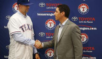 Newly signed Texas Rangers pitcher Mike Minor shakes hands with Texas Rangers General Manager Jon Daniels during a press conference at Globe Life Park in Arlington, Texas, Wednesday, Dec. 6, 2017. A day after meeting in Los Angeles with Japanese pitcher and outfielder Shoehi Ohtani, Rangers officials were back home in Texas and introduced left-hander Mike Minor. The likely starter signed a $28 million, three-year contract. (Rose Baca/The Dallas Morning News via AP)