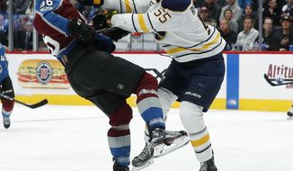 Buffalo Sabres defenseman Rasmus Ristolainen, right, of Finland, checks Colorado Avalanche right wing Mikko Rantanen, of Finland, as he loses control of the puck in the first period of an NHL hockey game Tuesday, Dec. 5, 2017, in Denver. (AP Photo/David Zalubowski)