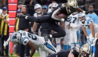 FILE - In this Sunday, Dec. 3, 2017, file photo, New Orleans Saints running back Alvin Kamara (41) leaps over Carolina Panthers cornerback Daryl Worley (26) in the second half of an NFL football game in New Orleans.  When the first-place New Orleans Saints face the Atlanta Falcons on Thursday night in an NFC South matchup with serious playoff ramifications, the spotlight will be on the guys in the backfield. ( (AP Photo/Bill Feig)