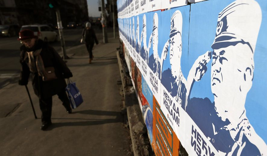 A woman passes by posters showing former Bosnian Serb wartime general Ratko Mladic, reading: ''I won't betray!'', in Belgrade, Serbia, Wednesday, Dec. 6, 2017. A U.N. court has convicted former Bosnian Serb military chief Gen. Ratko Mladic of genocide and crimes against humanity and sentenced him to life in prison for atrocities perpetrated during Bosnia's 1992-1995 war. (AP Photo/Darko Vojinovic)