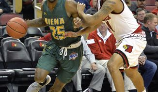 Siena guard Nico Clareth (25) attempts to drive around the defense of Louisville guard Quentin Snider (4) during the first half of an NCAA college basketball game, Wednesday, Dec. 6, 2017, in Louisville, Ky. (AP Photo/Timothy D. Easley)