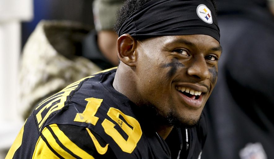 FILE - In this Nov. 16, 2017, file photo, Pittsburgh Steelers wide receiver JuJu Smith-Schuster (19) smiles on he sideline during an NFL football game against the Tennessee Titans, in Pittsburgh. Pittsburgh Steelers rookie wide receiver JuJu Smith-Schuster and Cincinnati Bengals cornerback George Iloka have been suspended one game each by the NFL for violating league safety rules. Smith-Schuster was flagged for unnecessary roughness and taunting after a blindside hit on Bengals linebacker Vontaze Burfict in the fourth quarter of Pittsburgh's 23-20 victory Monday night, Dec. 5. Iloka was penalized for unnecessary roughness for a helmet-to-helmet hit on Steelers wide receiver Antonio Brown. (AP Photo/Keith Srakocic, File) **FILE**